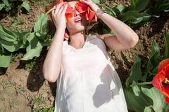 La femme sexy chaude se situant dans les tulipes mettent en place couvrir ses yeux d'écoulement Photos stock