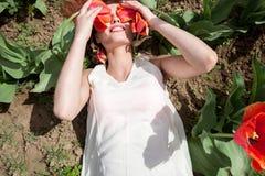 La femme sexy chaude se situant dans les tulipes mettent en place couvrir ses yeux d'écoulement Photographie stock libre de droits