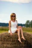La femme sexy de mode dans des lunettes de soleil et le blanc s'habillent sur la meule de foin Photo stock