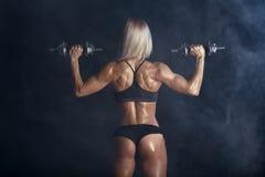 La femme sexy forte s'exerce avec des barbells Photographie stock