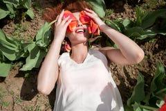 La femme sexy magnifique couvrant ses yeux dans les tulipes rouges mettent en place Photos stock