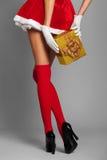 La femme sexy s'est habillée dans la robe rouge de Noël avec le boîte-cadeau photos libres de droits