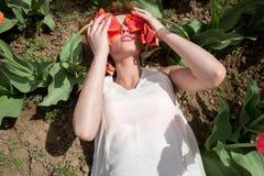 La femme sexy se situant dans les tulipes mettent en place couvrir ses yeux de fleurs Photographie stock libre de droits