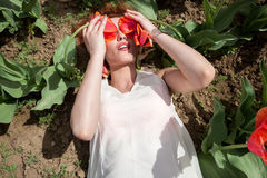 La femme sexy se situant dans les tulipes mettent en place couvrir ses yeux de fleurs Photo stock
