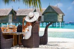 La femme snob s'assied à une table de déjeuner installée sur une plage en Maldives photos stock