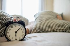 La femme somnolente atteignant tenant le réveil pendant le matin avec en retard se réveillent photographie stock
