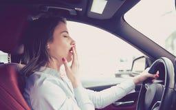 La femme somnolente conduisant sa voiture après voyage de longue heure a isolé le fond de rue images stock