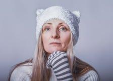La femme songeuse avec le regard attentif dans le chapeau drôle avec des oreilles et les gants rayés regardent calmes la caméra,  image libre de droits