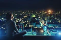 La femme songeuse regarde la ville de nuit Photos libres de droits