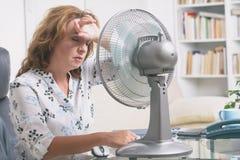La femme souffre de la chaleur dans le bureau ou à la maison Photos libres de droits