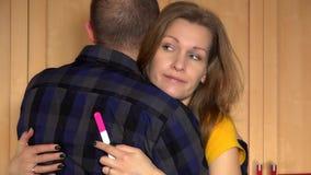 La femme soumise à une contrainte avec l'essai de grossesse positif étreignent son homme et pensent banque de vidéos