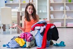 La femme soumise à une contrainte faisant la blanchisserie à la maison images stock