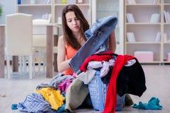 La femme soumise à une contrainte faisant la blanchisserie à la maison image stock