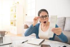 La femme soumise à une contrainte panique vérifiant des factures Image libre de droits