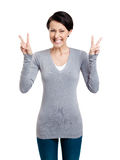 La femme souriante affiche le signe de victoire avec deux mains image stock