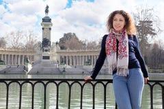 La femme sourit et se penche sur la balustrade au fond du monument Images stock