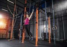 La femme sportive établit au gymnase avec la barre photo stock