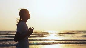La femme sportive adaptée pulse sur la plage au coucher du soleil clips vidéos
