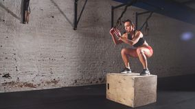 La femme sportive convenable enferme dans une boîte des sauts dans le gymnase abandonné d'usine L'exercice intense fait partie de banque de vidéos