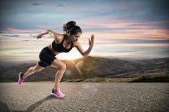 La femme sportive court sur la rue pendant le coucher du soleil image stock