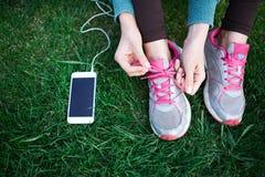 La femme sportive dans les vêtements de sport s'assied avec le smartphone sur l'herbe en parc et attache des dentelles sur des es Photo stock