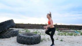 La femme sportive dans une agrostide blanche et des guêtres noires exécute des exercices de force utilisant une grande roue lourd clips vidéos