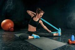 La femme sportive de brune s'exerçant avec la bande en caoutchouc photographie stock libre de droits