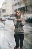 La femme sportive et heureuse la tenant distribue pour attraper des baisses de pluie Images stock