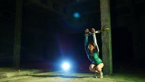 La femme sportive et sexy exécute des exercices avec le système de trx de forme physique, courroies de suspension de TRX La nuit, clips vidéos