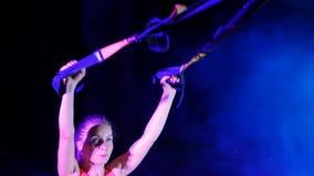 La femme sportive et sexy exécute des exercices avec le système de trx de forme physique, courroies de suspension de TRX La nuit, banque de vidéos