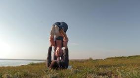 La femme sportive faisant l'acroyoga équilibre sur des mains de son associé masculin sur le pré sur le fond du ciel clips vidéos