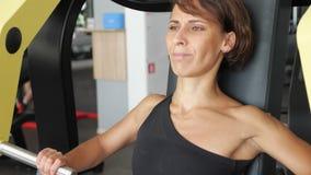 La femme sportive fait des exercices pour des muscles de bras sur la machine s'exerçante banque de vidéos