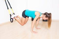 La femme sportive fait l'exercice de jambes de trx photographie stock