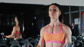 La femme sportive forme des muscles des mains bodybuilding femelle banque de vidéos