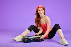 La femme sportive gaie s'assied après la formation de forme physique, arrêtant le joueur audio portatif images stock