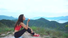 La femme sportive mange la pomme rouge après séance d'entraînement sur la montagne Vue aérienne de stupéfier de belles montagnes  clips vidéos