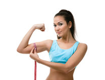 La femme sportive mesure son biceps Photographie stock libre de droits