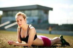 La femme sportive se trouve sur le champ après la séance d'entraînement extérieure photos stock