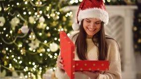 La femme stupéfaite heureuse en Santa Hat, jugeant actuel dans des ses mains, l'ouvre et sourit Jolie brune avec de longs cheveux clips vidéos