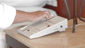 La femme supérieure adulte non reconnue dans un peignoir blanc prend le téléphone dans la chambre d'hôtel et presse le levier len banque de vidéos