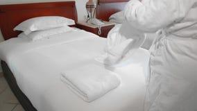 La femme supérieure adulte non reconnue prend une serviette blanche se trouvant sur un lit dans une chambre d'hôtel Le concept du banque de vidéos