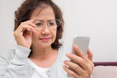 La femme supérieure asiatique est inquiétée avec le nouveau message sur son phone Photos stock