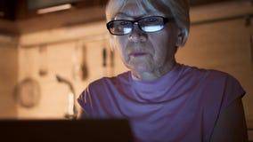 La femme supérieure avec des verres travaillent sur l'ordinateur portable du maison-bureau la nuit La femme d'affaires a mis dess banque de vidéos