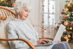 La femme supérieure avec du charme utilise l'ordinateur à la maison Images libres de droits