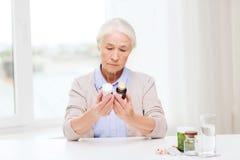 La femme supérieure avec la médecine cogne à la maison Photographie stock libre de droits