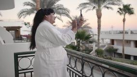 La femme supérieure caucasienne de sourire prend la photo de selfie sur le smartphone Il devrait être sur la terrasse de l'hôtel  banque de vidéos
