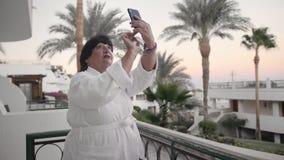 La femme supérieure caucasienne prend des photos sur un smartphone Il devrait être sur la terrasse de l'hôtel dans une robe longu banque de vidéos