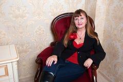 La femme supérieure dans la robe rouge s'assied sur la chaise Images libres de droits