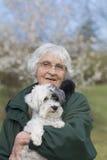 La femme supérieure de sourire avec son chien se garent au printemps Photo libre de droits