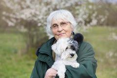 La femme supérieure de sourire avec son chien se garent au printemps Photos libres de droits